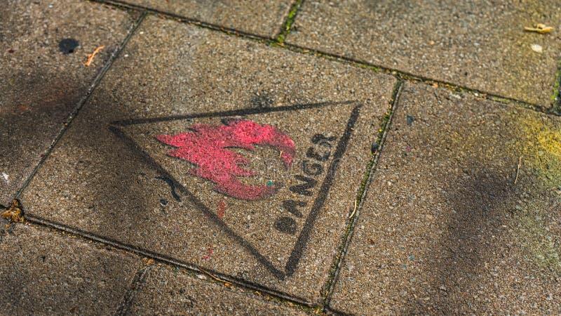 Sinal 'do perigo 'carimbado no pavimento em Ghent, Bélgica imagens de stock royalty free