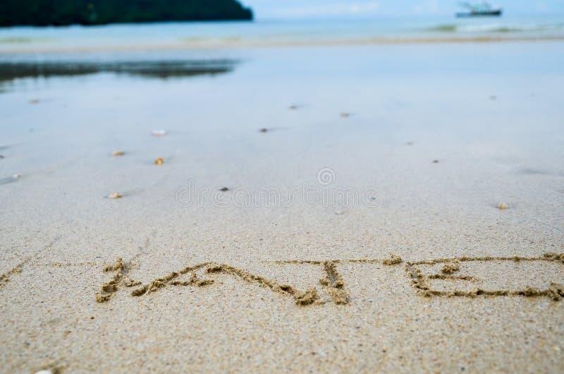 Sinal abstrato do ódio da palavra escrito em um fundo da praia da areia fotografia de stock royalty free