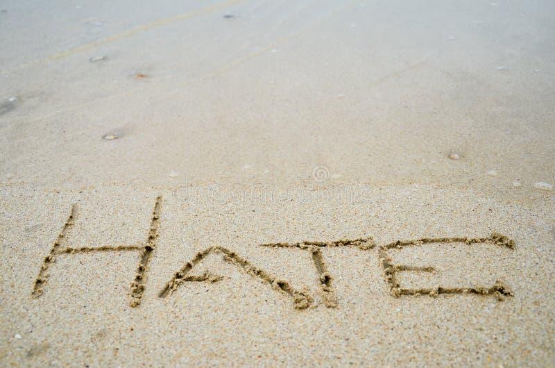 Sinal abstrato do ódio da palavra escrito em um fundo da praia da areia fotografia de stock