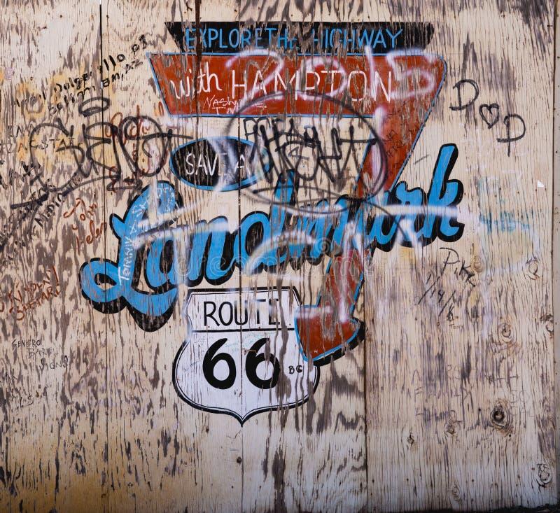Sinal afligido velho Route 66 da madeira compensada com grafittis foto de stock