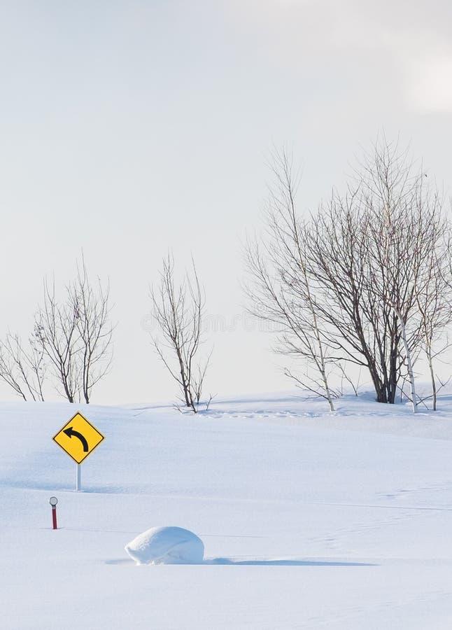 Sinal amarelo brilhante da curva à esquerda colocado e afogado em um campo nevado com as árvores desencapadas no fundo imagens de stock
