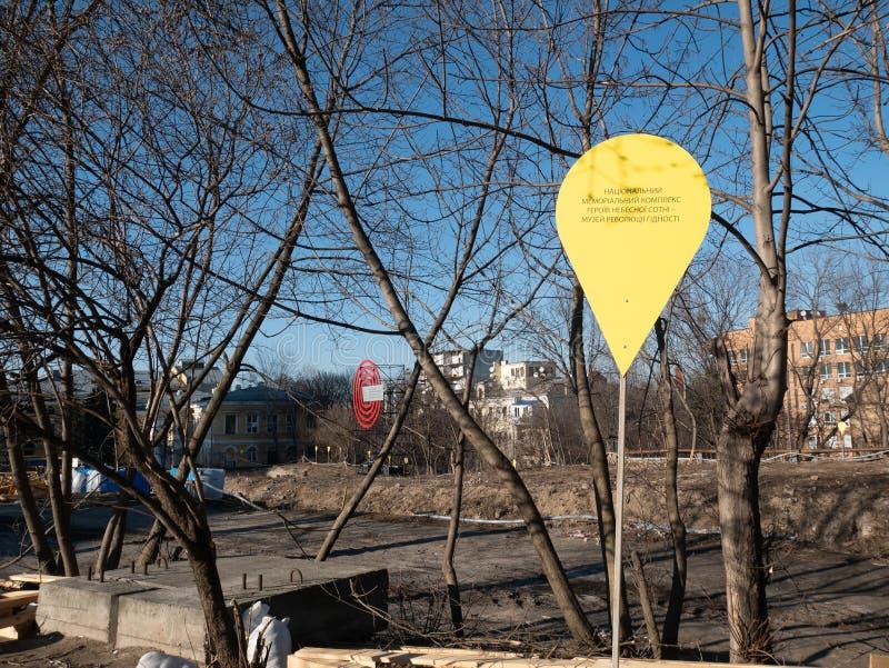 Sinal amarelo do canteiro de obras com o monumento da inscrição de cem memórias celestial da revolução da dignidade em Kiev imagem de stock royalty free
