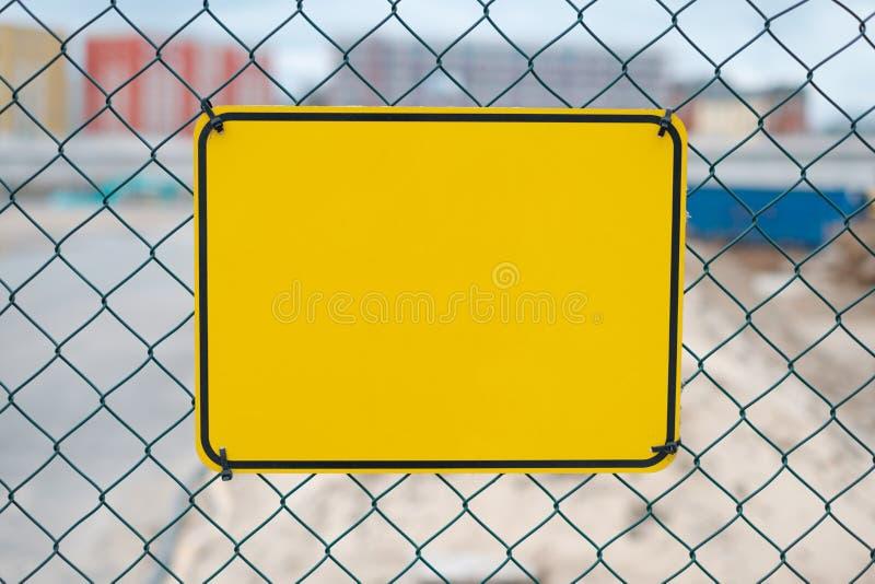 Sinal amarelo vazio na cerca do canteiro de obras - modelo do sinal de aviso fotos de stock