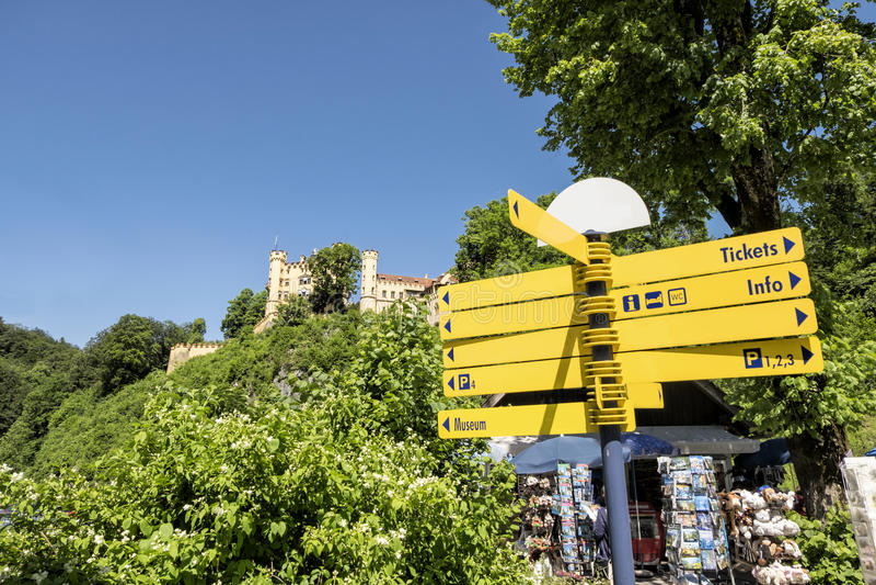 Sinal amarelo vazio na frente da loja de lembrança com o castelo de Hohenschwangau no monte imagem de stock