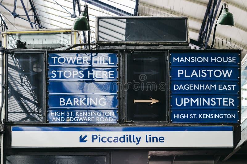 Sinal antiquado no subterrâneo de Londres na estação da corte do ` s do conde que aponta para destinos dentro da rede do tubo de  imagem de stock royalty free