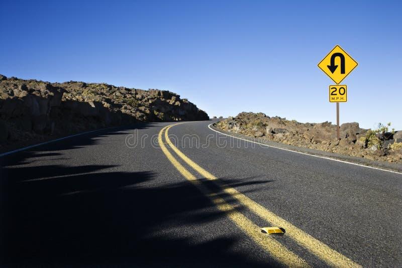 Sinal ao longo de uma curva em uma estrada. fotografia de stock royalty free