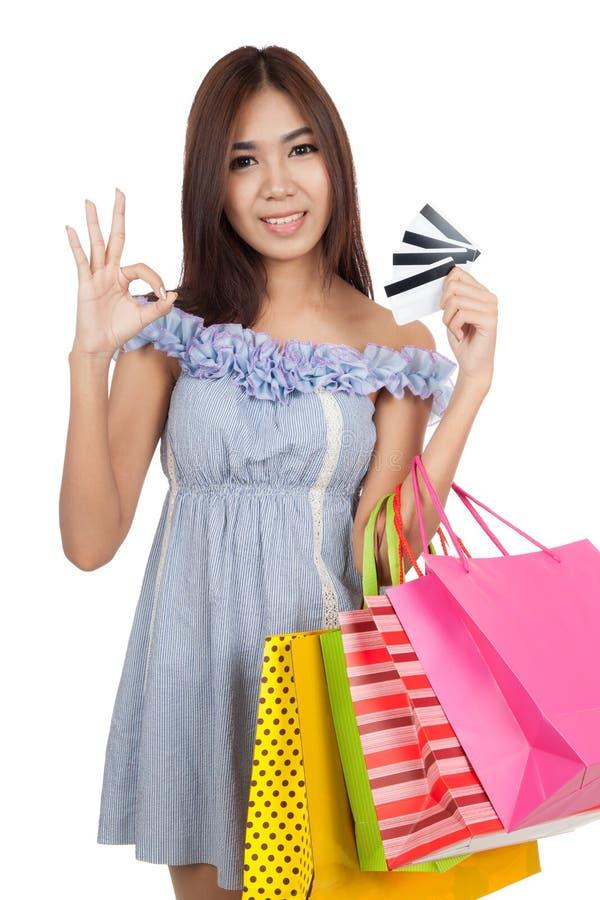 Sinal asiático bonito da APROVAÇÃO da mostra da mulher com muitos cartões de crédito foto de stock royalty free