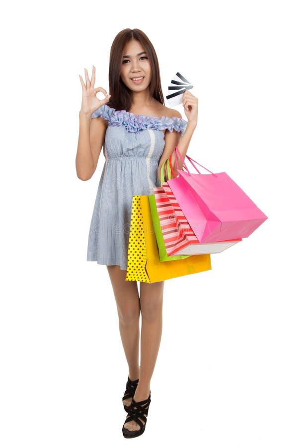 Sinal asiático bonito da APROVAÇÃO da mostra da mulher com muitos cartões de crédito imagem de stock royalty free