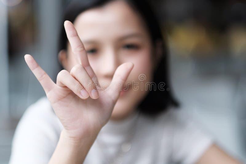 Sinal asiático da mão do amor da mostra da menina fotos de stock royalty free