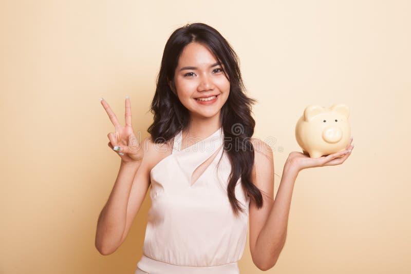 Sinal asiático da vitória da mostra da mulher com o banco de moeda do porco foto de stock royalty free