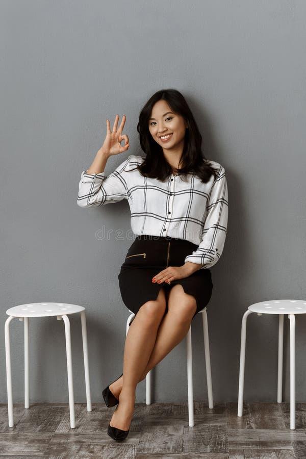 sinal asiático de sorriso da aprovação da exibição da mulher de negócios ao esperar fotos de stock