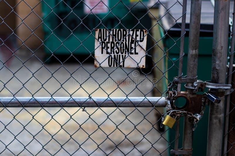 Sinal autorizado dos pessoais em uma cerca do elo de corrente com contentores imagem de stock