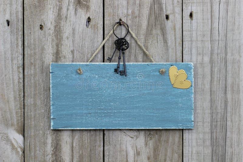 Sinal azul antigo que pendura na porta de madeira com corações e chaves do ferro fotografia de stock royalty free