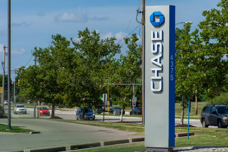 Sinal azul de Chase Bank com movimentação completamente, atm e flores na grama verde e no céu azul foto de stock royalty free