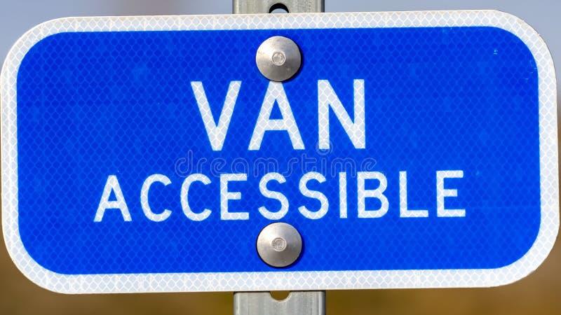 Sinal azul do panorama claro com um texto de Van Accessible em uma área de estacionamento para povos deficientes fotografia de stock royalty free