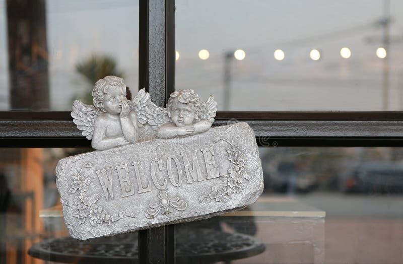 Sinal bem-vindo na pedra contra a porta de vidro do restaurante foto de stock