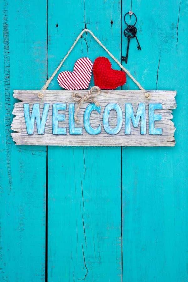 Sinal bem-vindo que pendura na porta de madeira envelhecida imagem de stock royalty free