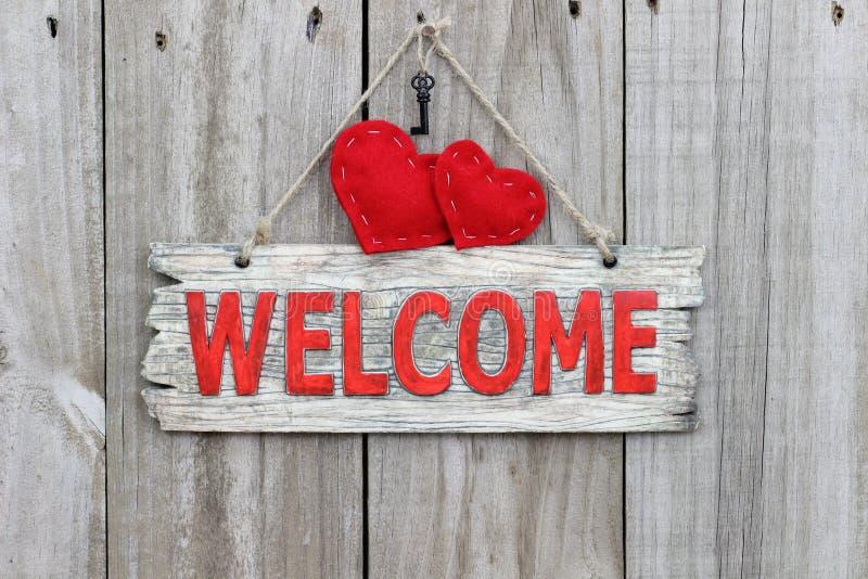 Sinal bem-vindo vermelho que pendura na porta de madeira com corações e chaves vermelhos do ferro fotos de stock royalty free