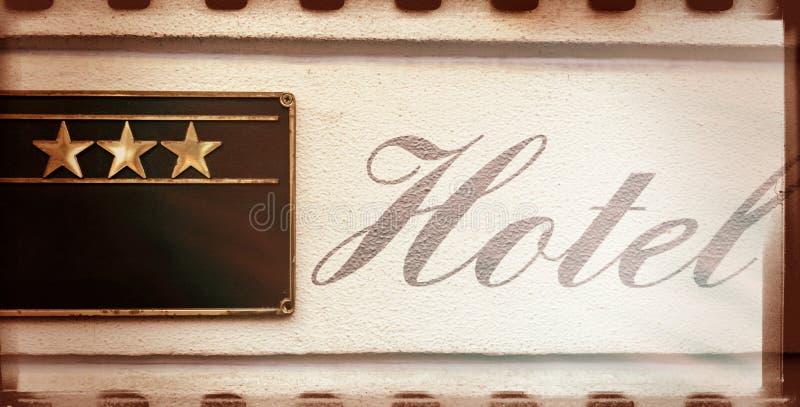 Sinal bonito da caligrafia do HOTEL ao lado da fachada de três estrelas imagens de stock