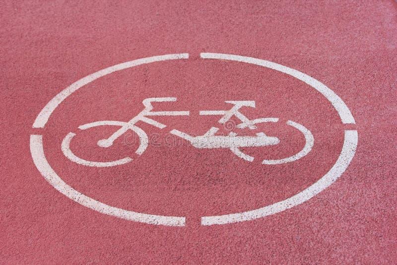 Sinal branco da bicicleta no trajeto vermelho da bicicleta imagem de stock royalty free