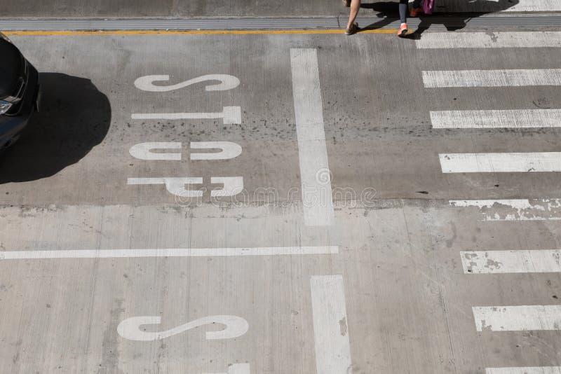 sinal branco da PARADA do tráfego no motorista do preto do cuidado da rua parar na linha do cruzamento, faixa de travessia de cru fotografia de stock