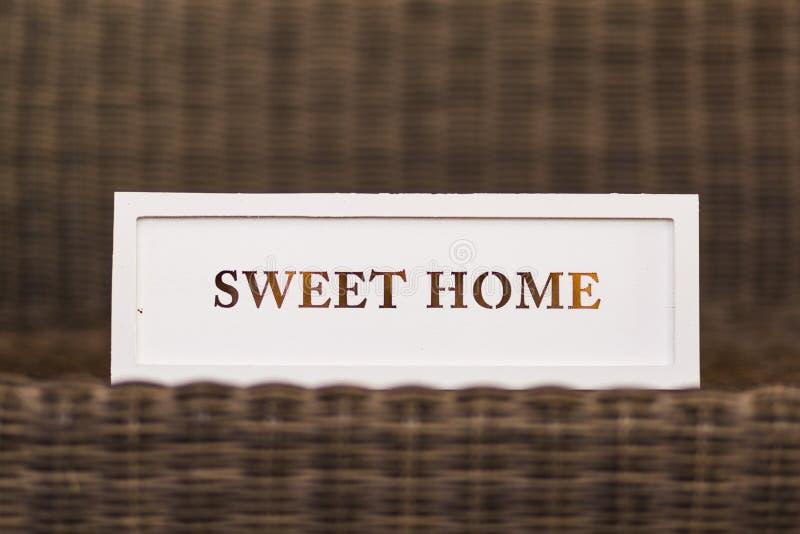 Sinal branco home doce no fundo de madeira do vintage Casa e lifes fotografia de stock royalty free