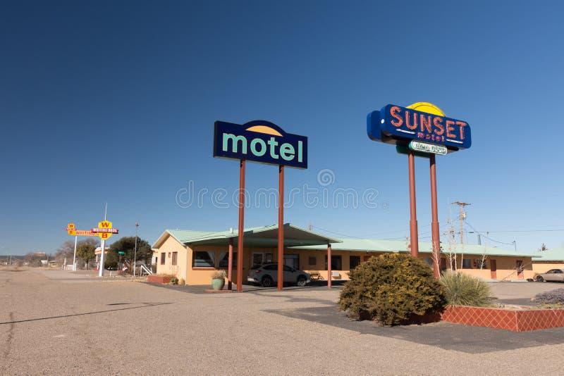 Sinal colorido do motel do por do sol com pescadas Bros posto de gasolina no fundo imagens de stock royalty free