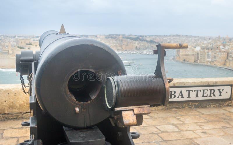 Sinal com rotulação da bateria em uma parede nos jardins superiores de Barrakka com uma arma pesada no primeiro plano fotografia de stock