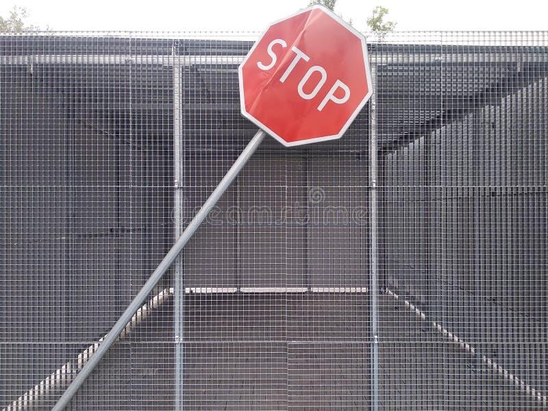 Sinal curvado da parada perto da construção feita da malha do ferro as consequências de uma colisão, acidente segurança rodoviári ilustração do vetor