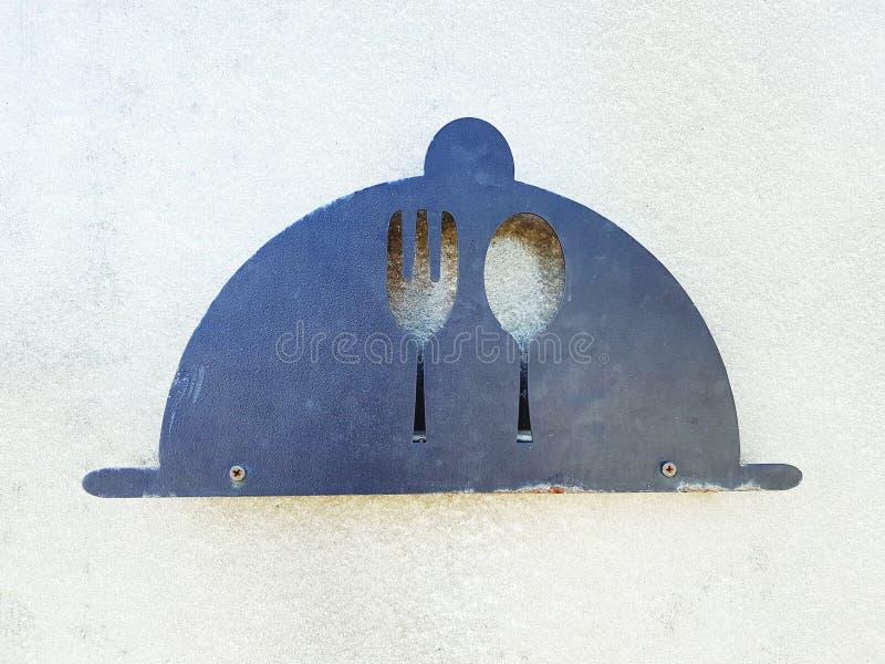 Sinal da colher e da forquilha feito do a?o ou do ferro no fundo da parede do cimento branco foto de stock