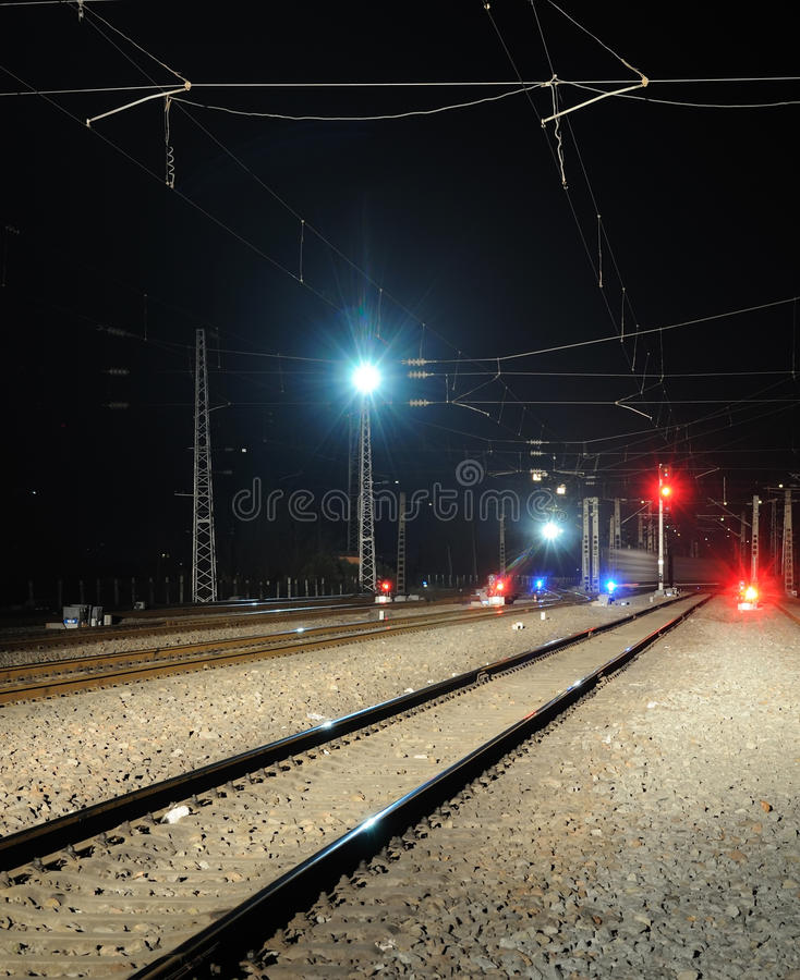 Sinal da estrada de ferro e do trem na noite imagens de stock