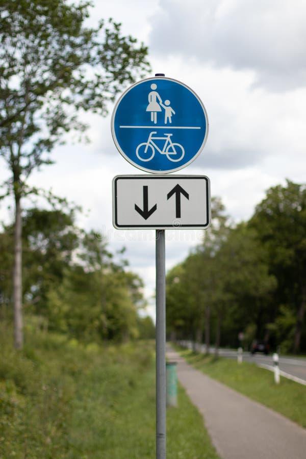 Sinal da maneira da passagem e da bicicleta, seta para ambos sentido foto de stock