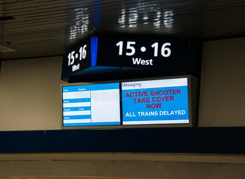 Sinal da mensagem do estação de caminhos de ferro que indica que os trens são atrasado devido a um atirador ativo fotografia de stock royalty free