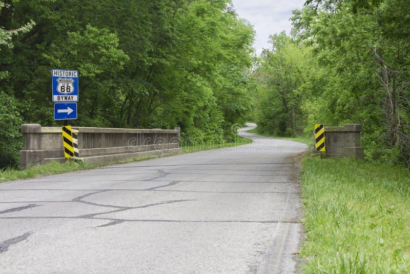 Sinal da rota 66 ao longo de um estiramento do enrolamento da estrada fotos de stock royalty free