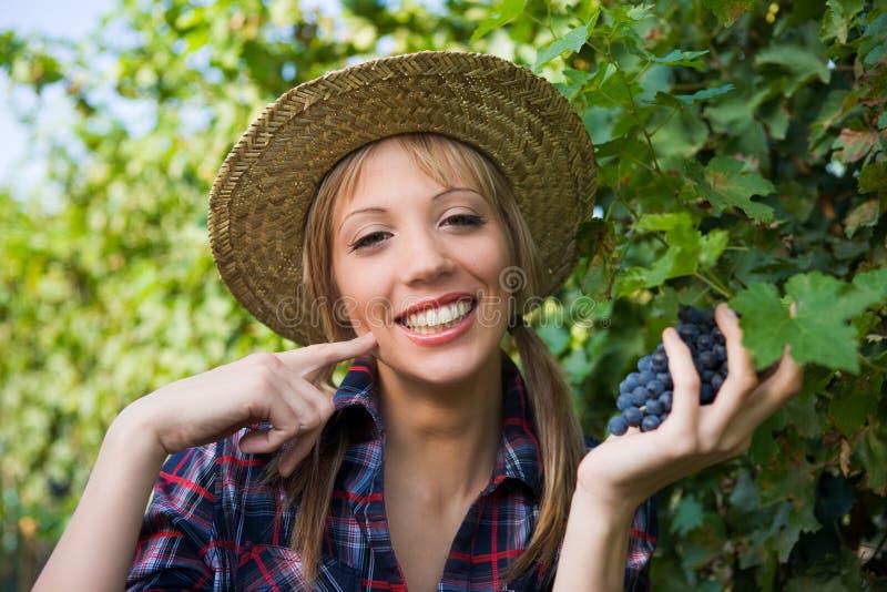 Sinal da uva do camponês da mulher nova bom com mão imagens de stock royalty free