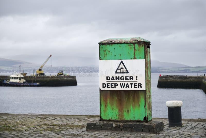 Sinal das águas profundas do perigo na doca do porto do mar na estrutura e em barcos verdes no fundo foto de stock royalty free