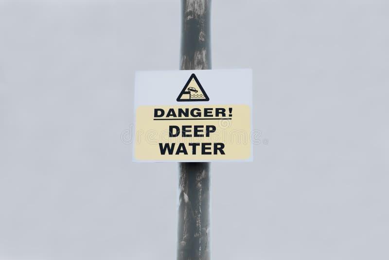 Sinal das águas profundas do perigo no cargo contra o fundo do céu no porto do mar imagem de stock royalty free