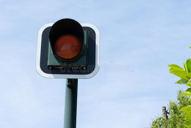 Sinal de sinal alaranjado de piscamento amarelo para o fundo do céu azul dos carros imagem de stock