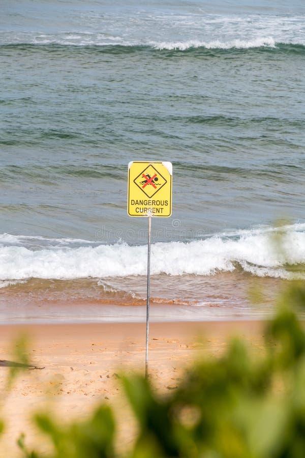 Sinal de aviso atual perigoso, nenhuma natação no mar fotos de stock royalty free