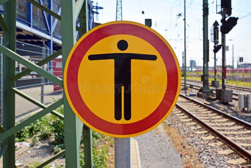 Sinal de aviso com a pessoa na extremidade da plataforma do trem fotografia de stock