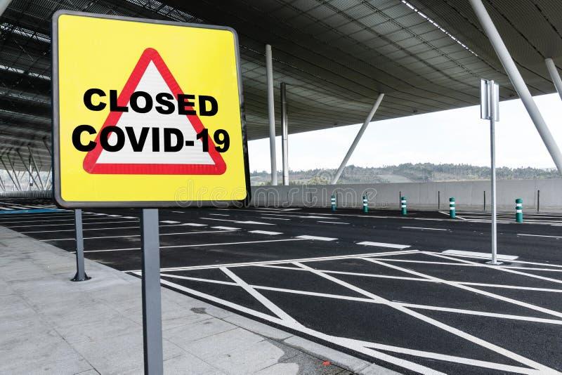 Sinal de aviso com texto CLOSED COVID-19 num estacionamento vazio de um aeroporto ou estação de comboios fotos de stock