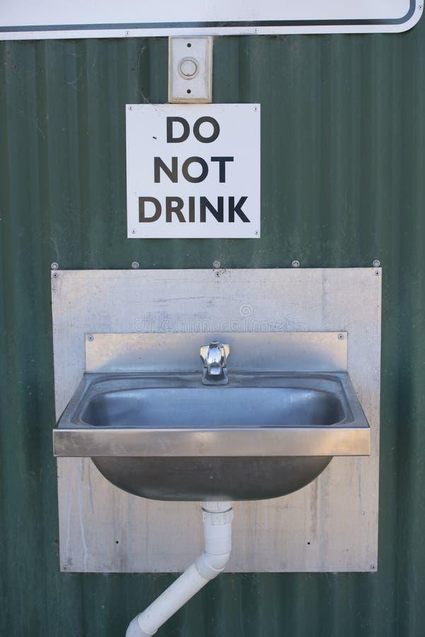 Sinal de aviso da água potável na aba furada da água imagens de stock