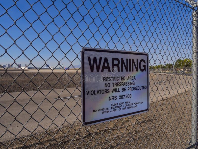 Sinal de aviso em uma cerca ao aeroporto internacional de McCarran - LAS VEGAS - NEVADA - 12 de outubro de 2017 imagem de stock royalty free