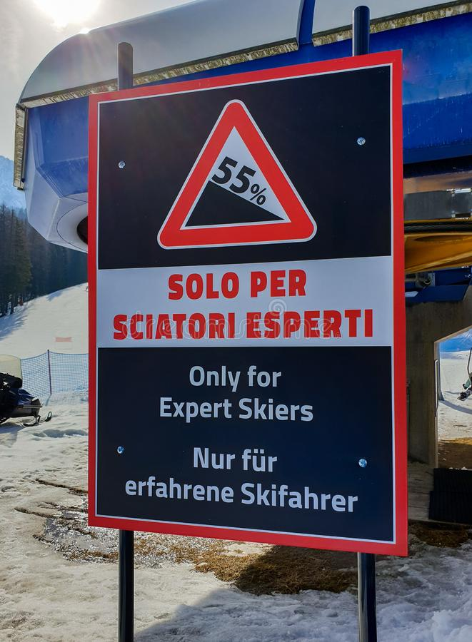 Sinal de aviso em uma inclinação do esqui somente para os esquiadores peritos em Cortina d'Ampezzo, dolomites, Itália fotos de stock