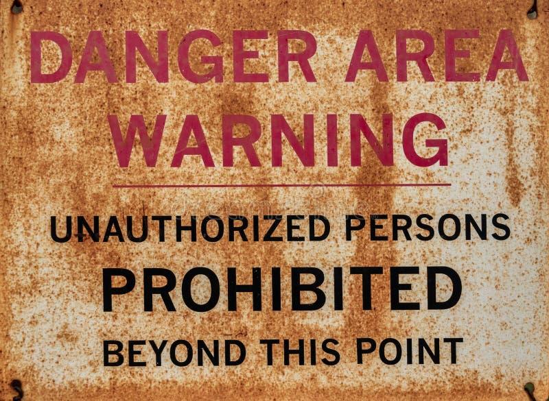 Sinal de aviso oxidado com a inscrição: Zona de perigo, aviso, pessoas desautorizadas proibidas além deste ponto foto de stock