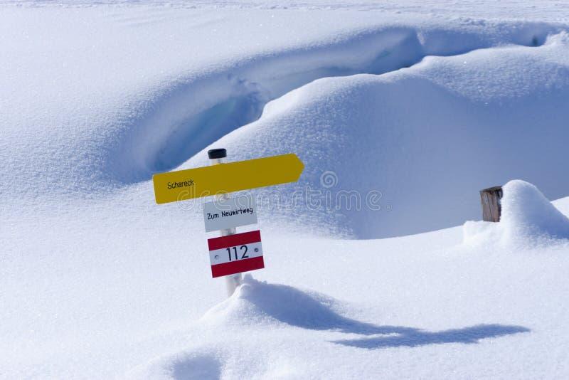 Sinal de caminhada amarelo na neve de Áustria fotografia de stock royalty free