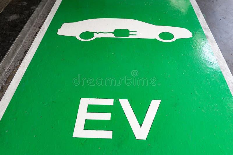 Sinal de encaixe branco do veículo com alfabeto EV no parque de estacionamento verde imagem de stock royalty free