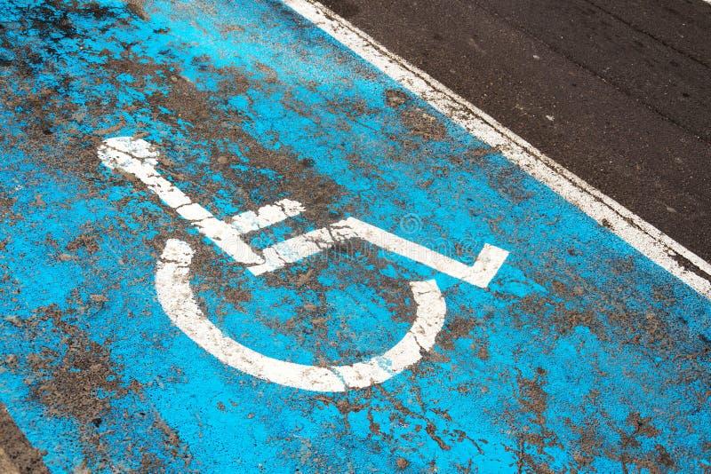 Sinal de estacionamento da desvantagem pintado na estrada no lugar de estacionamento para povos deficientes ou deficientes fotografia de stock royalty free