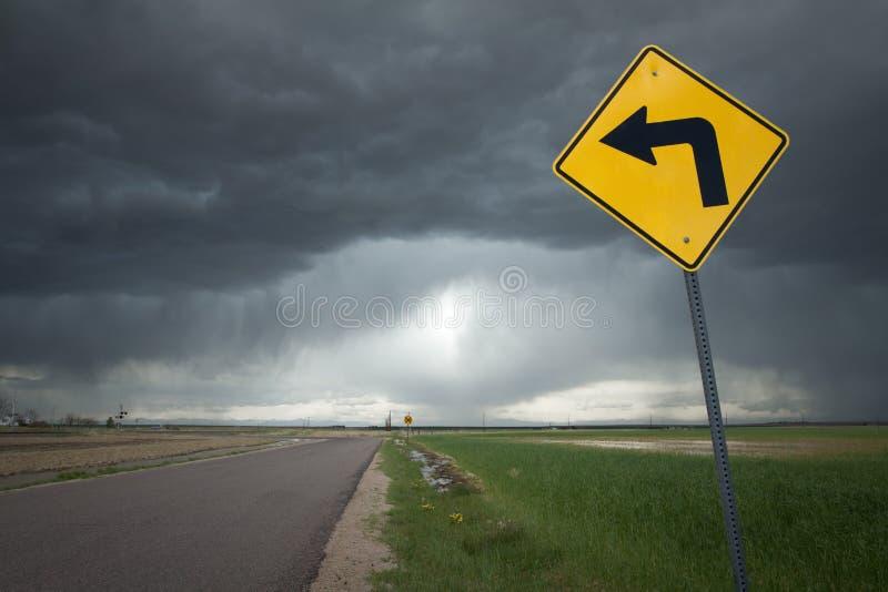 Sinal de estrada com seta da curva esquerda e fundo sinistro da tempestade fotografia de stock