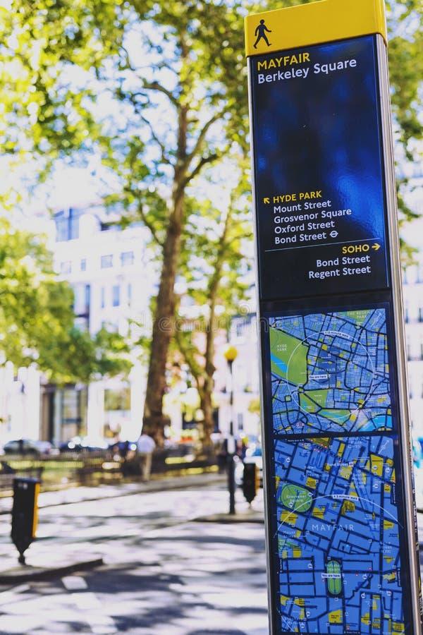 Sinal de estrada de Mayfair com o mapa no centro de cidade de Londres imagens de stock